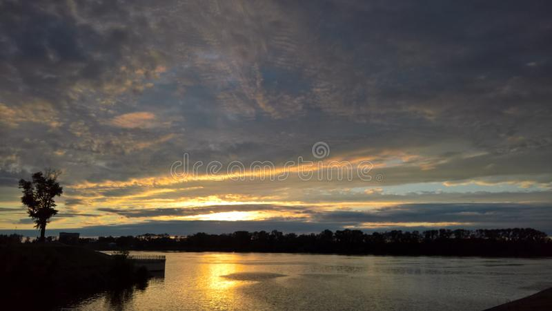 Solnedgång med att bedöva moln i staden av Uglich arkivfoto