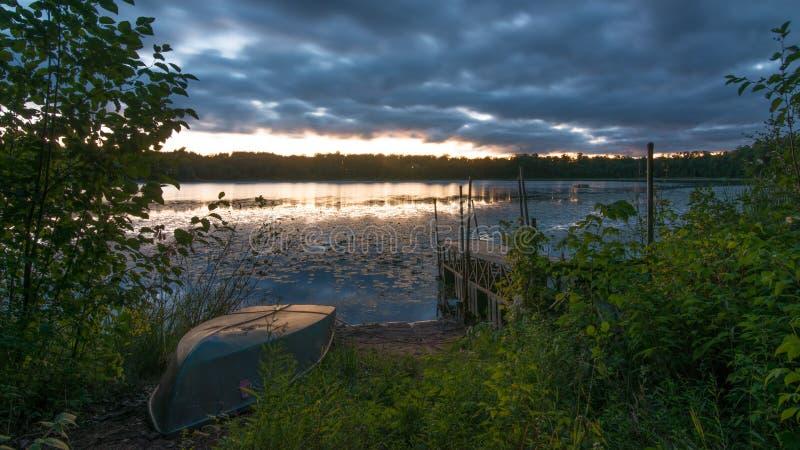 Solnedgång med den gamla skeppsdockan och det gamla radfartyget på den lilla avlägsna sjön i nordliga Wisconsin - moln och väder  arkivbilder
