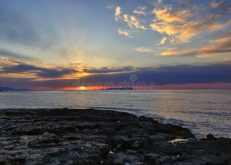 Solnedgång med det guld- ljusa härliga molnet på den svarta sandstranden i den sydostliga Island Kreta royaltyfri foto