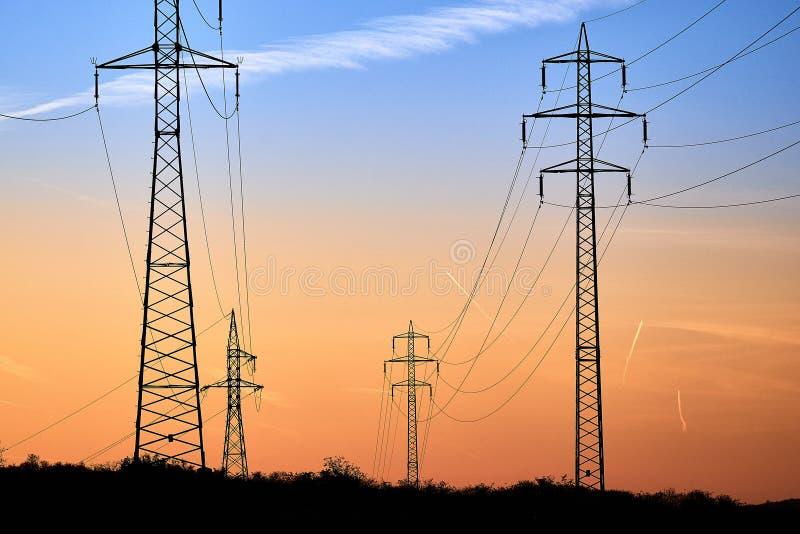 Solnedgång med en kontur av elektricitetspylonen och kraftledningar Södra Moravian för republiktown för cesky tjeckisk krumlov me arkivfoton