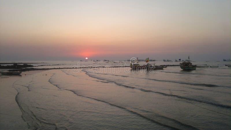 Solnedgång med fartyg på havskusten med vågor royaltyfri fotografi