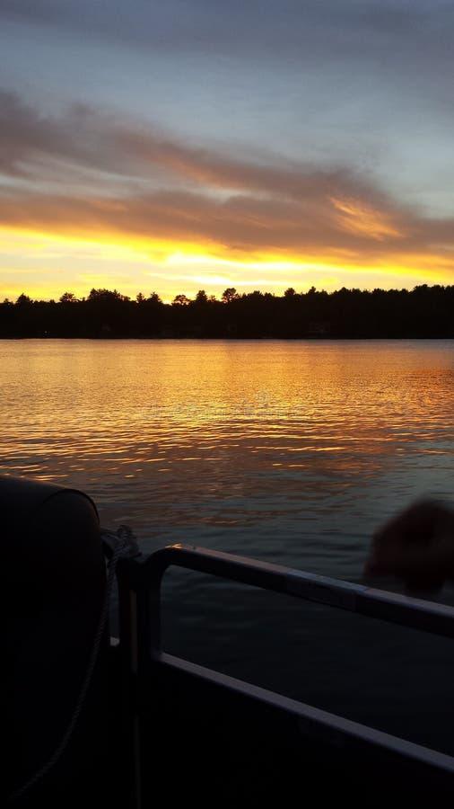 Solnedgång med fiskebåtar på sjön arkivbild