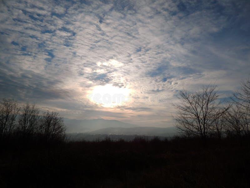 Solnedgång med fluffiga moln i himlen arkivbild