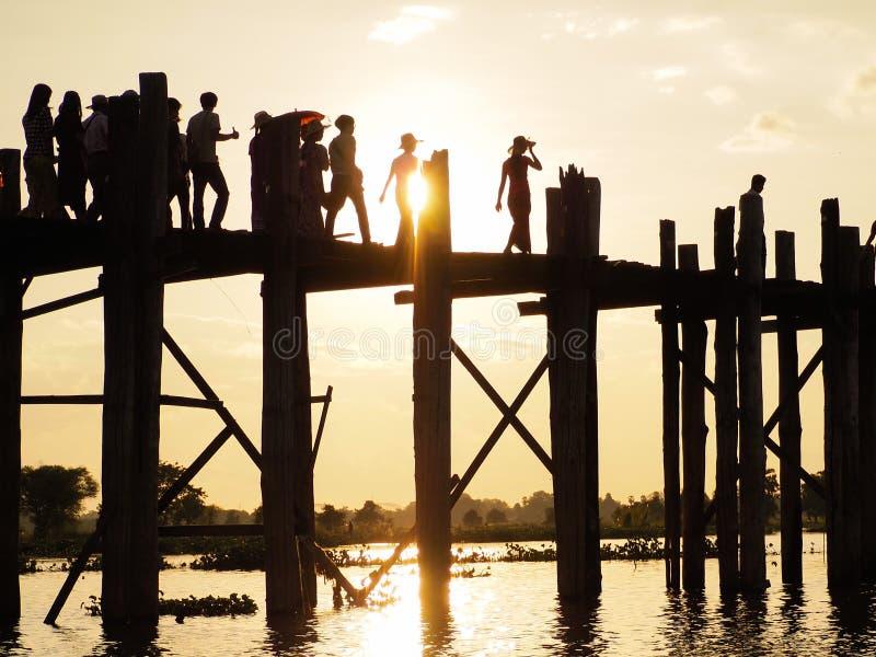 Solnedgång med konturn av folk som går på bron U-Bein arkivfoton