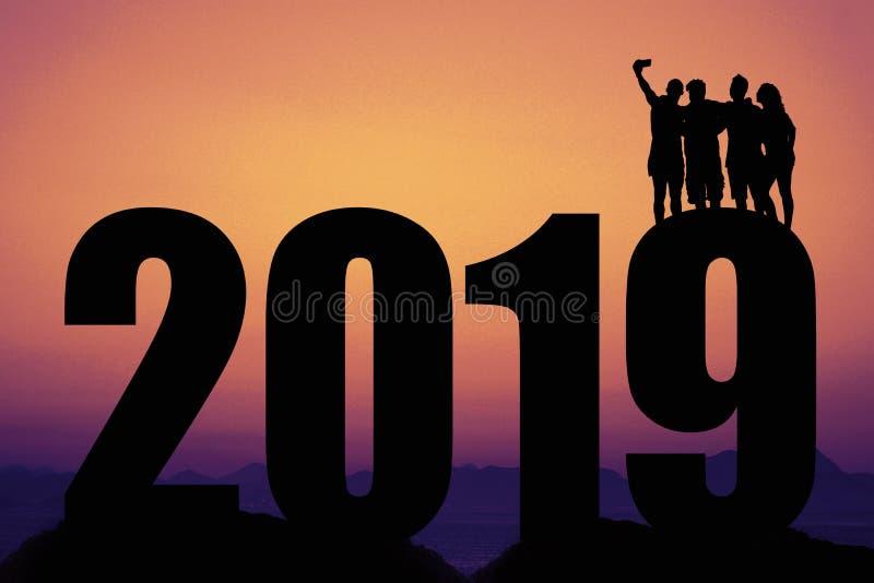 Solnedgång med konturn 2019 för nytt år med gruppen som tar en selfie arkivbilder