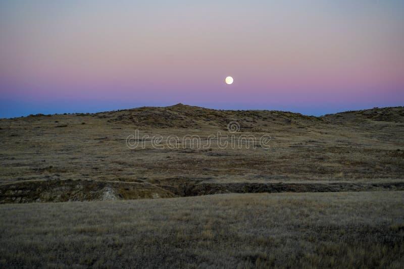 Solnedgång med månen och moonrise på de höga ökenslättarna royaltyfri fotografi