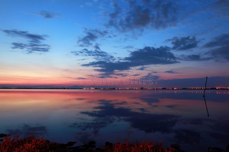 Solnedgång med reflexion royaltyfria bilder