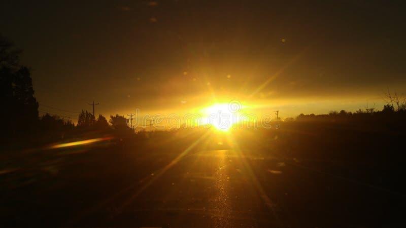 Solnedgång, medan köra till och med bergen arkivfoto