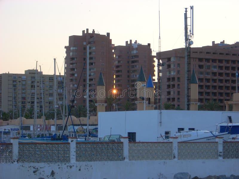 Solnedgång mellan byggnader på stranden royaltyfri foto