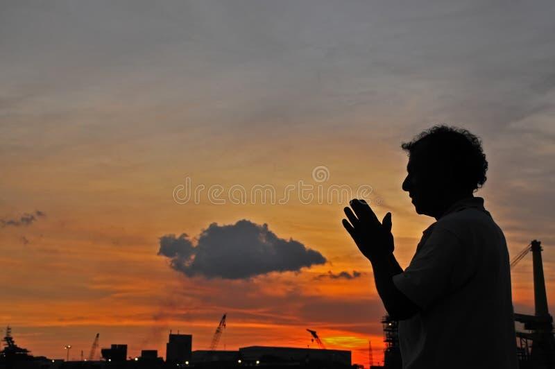 Solnedgång, moln och bön på sjösidan arkivfoto