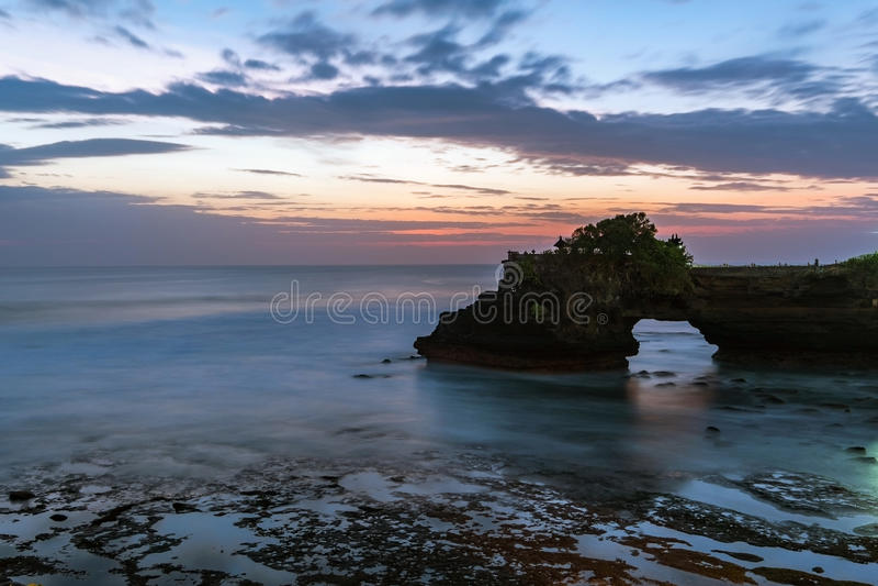 Solnedgång nära den berömda turist- gränsmärket av den Bali ön - Tanah lott- & Batu Bolong tempel royaltyfri bild