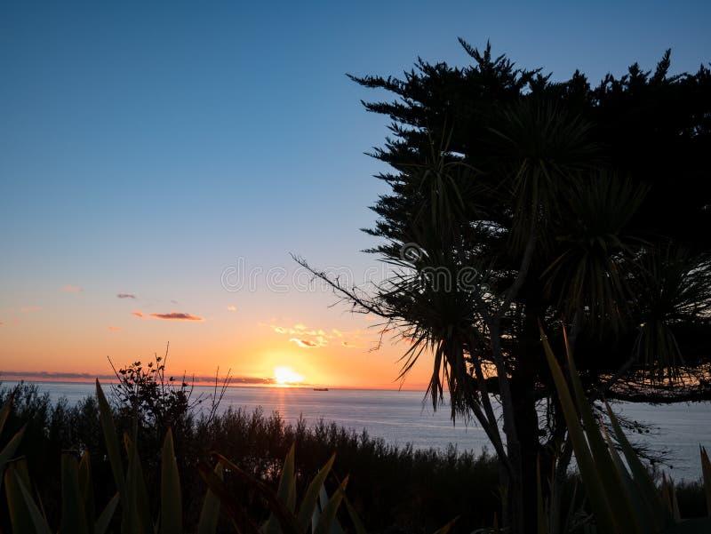 Solnedgång och att gömma i handflatan över havet arkivbilder