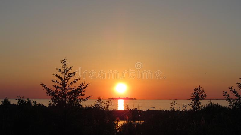 Solnedgång och den ensamma ön royaltyfri fotografi