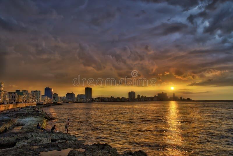 Solnedgång och dramatiska moln över havannacigarrhorisont med fiskare i förgrund arkivbilder