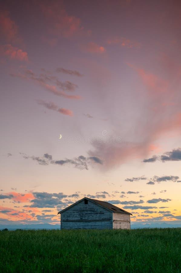 Solnedgång och ett par som överges och som är brutet ner lantgårdhus i de Alberta prärierna royaltyfria bilder