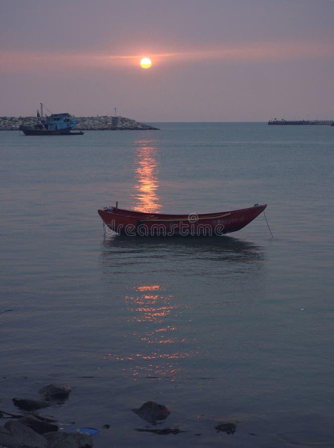 Solnedgång och fartyg på kusten royaltyfria foton