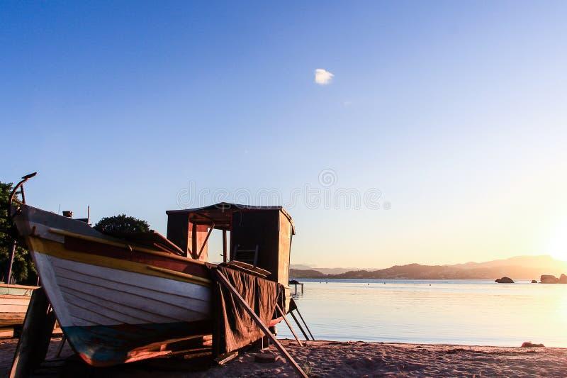 Solnedgång och fiskebåt på den Abraao stranden & x28en; Florianopolis - Brazil& x29; royaltyfri foto