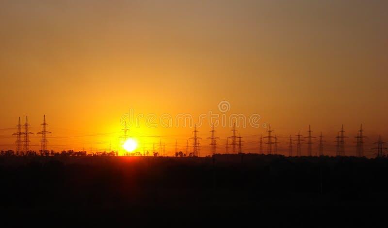 Solnedgång och kraftledningar royaltyfri fotografi