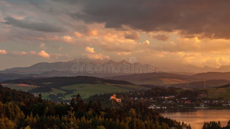 Solnedgång och moln över berg och sjön med byn arkivbild