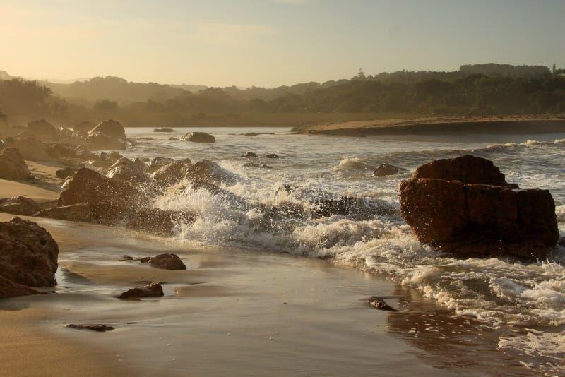 Solnedgång och plaskande våg på lagun arkivbilder
