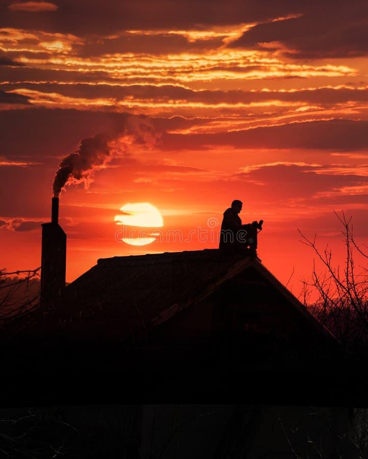 Solnedgång och silhuett av män och rök arkivfoto