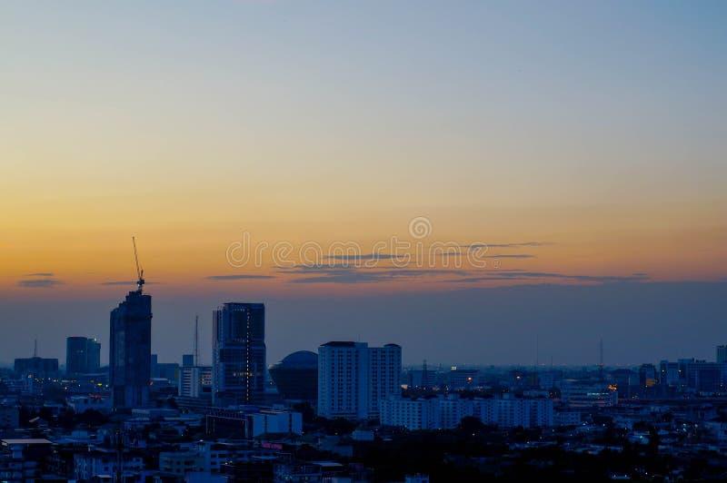 Solnedgång och stad arkivbild