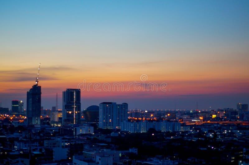 Solnedgång och stad arkivfoton