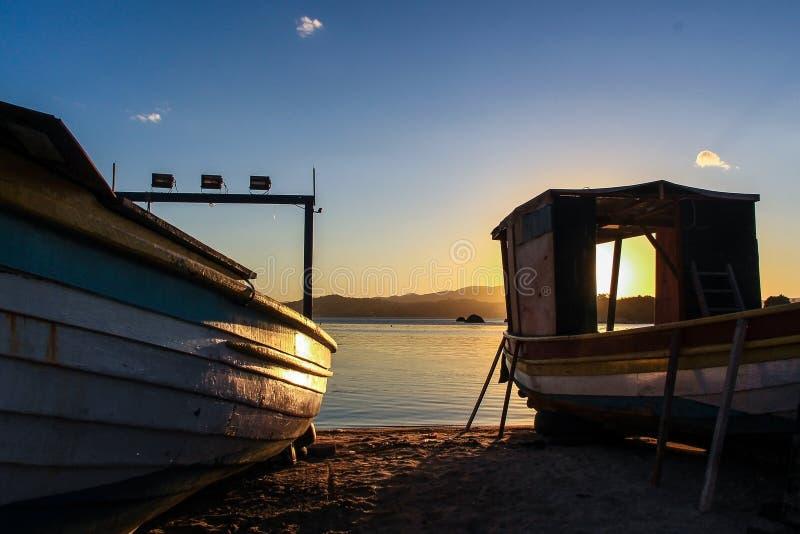 Solnedgång och två fiskebåtar på den Abraao stranden & x28en; Florianopolis - Brazil& x29; royaltyfria foton