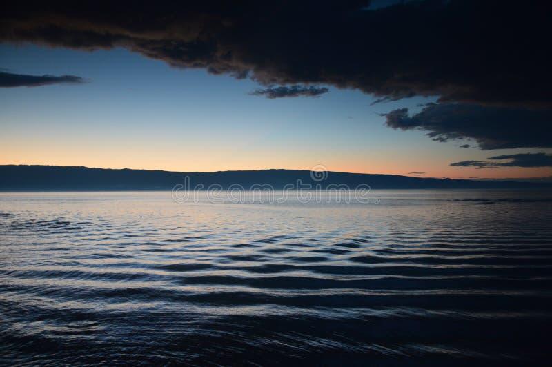 Solnedgång och virvlande runt vatten i sommar på Lake Baikal, Irkutsk region, rysk federation arkivfoton