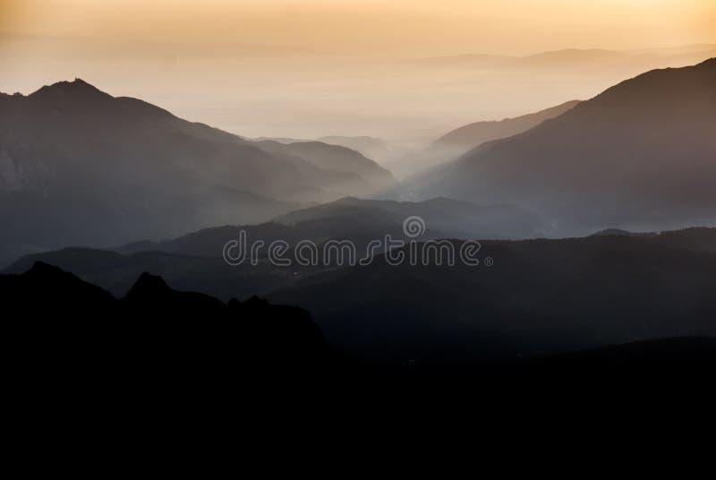 Solnedgång ovanför bergkanter och dalar royaltyfri bild
