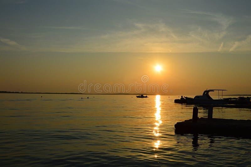 Solnedgång ovanför den Vrsi Mulo stranden i Kroatien, Adriatiskt havet med konturer av små fartyg, den synliga boj och moloen arkivbilder