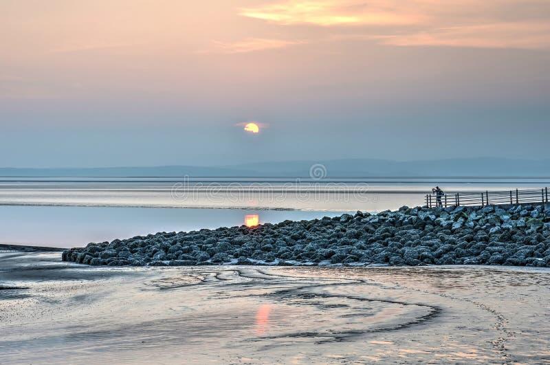Solnedgång ovanför en stenig pir arkivbilder