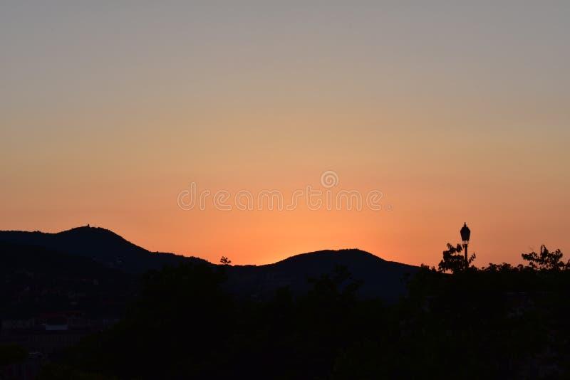 Solnedgång ovanför kullarna av Buda arkivbild