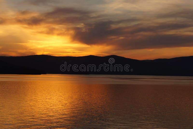 Solnedgång på bergsjön royaltyfria bilder