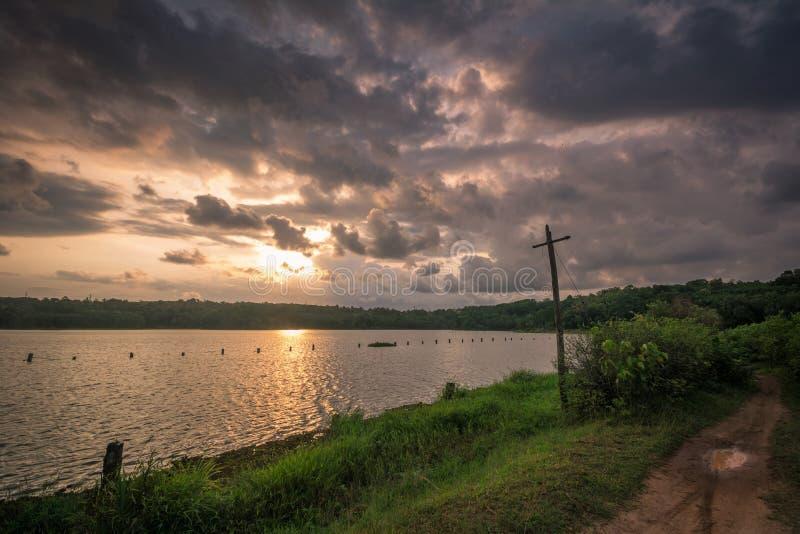Solnedgång på Cheloor lantgården för sjöfisk Sasthamcotta royaltyfria bilder