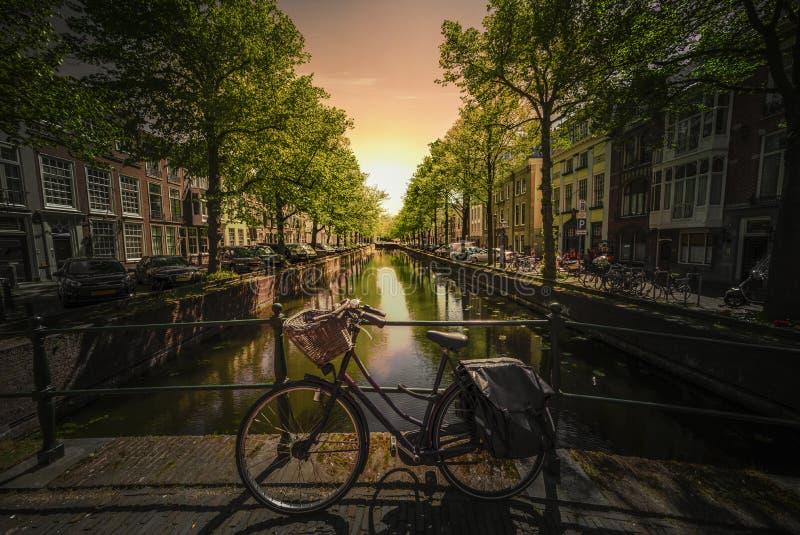 Solnedgång på cyklar på den Amsterdam bron royaltyfria bilder