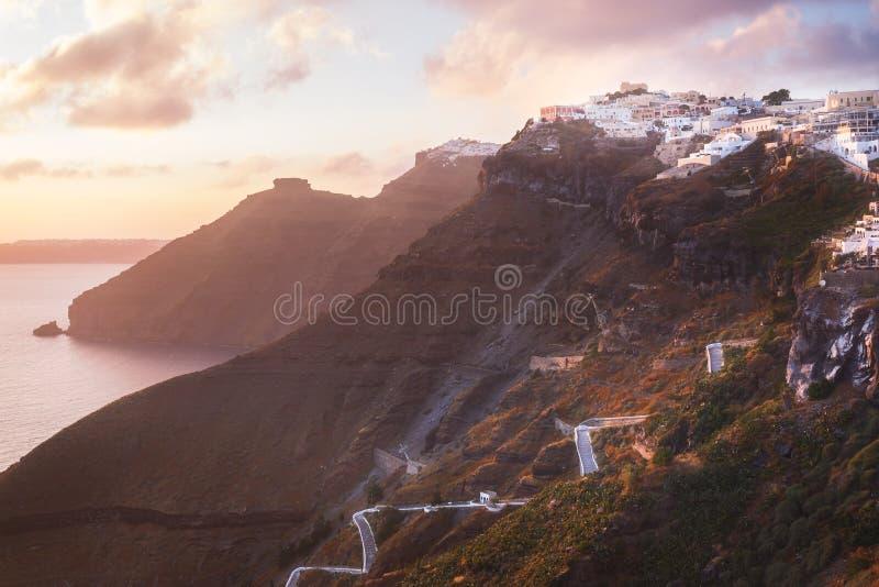 Solnedgång på den grekiska ön av Santorini, med färgrikt varmt ljus och moln över staden royaltyfria bilder
