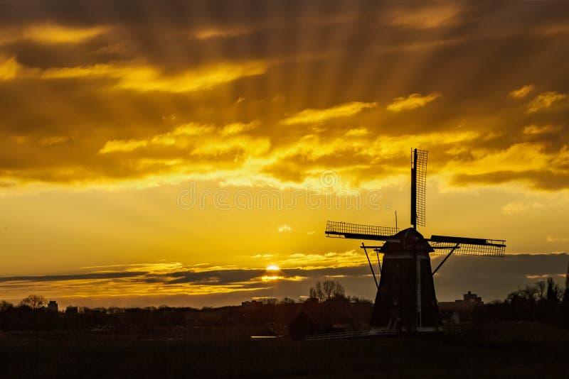 Solnedgång på den holländska väderkvarnen arkivbild