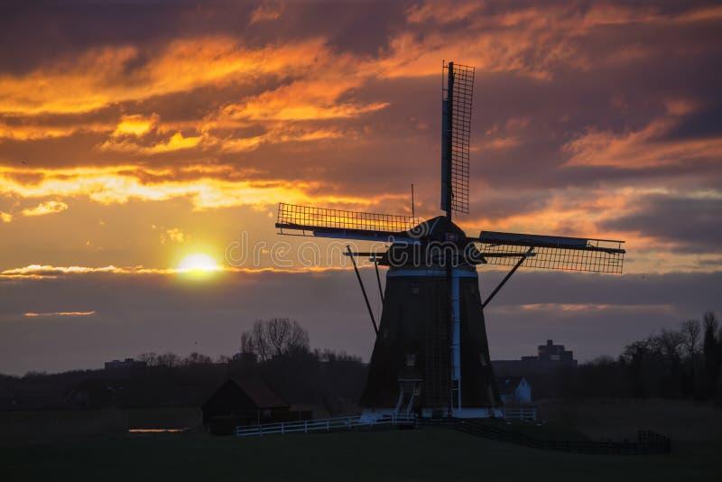 Solnedgång på den holländska väderkvarnen royaltyfri foto