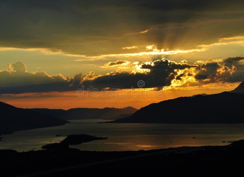 Solnedgång på den Kotor fjärden med solen som skiner bak molnen fotografering för bildbyråer