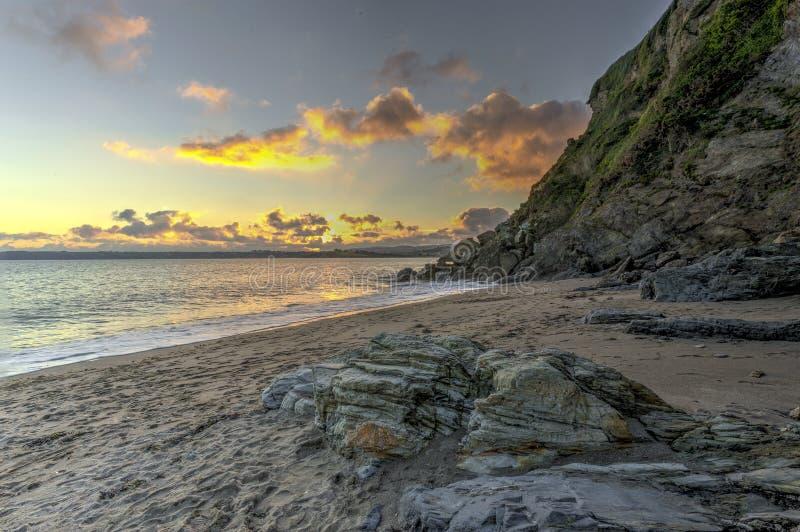 Solnedgång på den Polkerris stranden i Cornwall, England royaltyfri foto