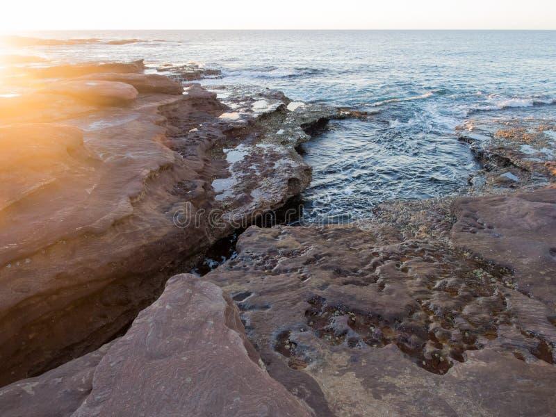 Solnedgång på den steniga stranden, röd bluff, Kalbarri, västra Australien arkivfoton
