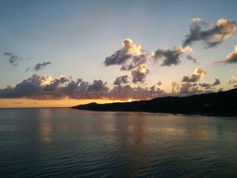 Solnedgång på den tropiska ön med moln och havet royaltyfria foton