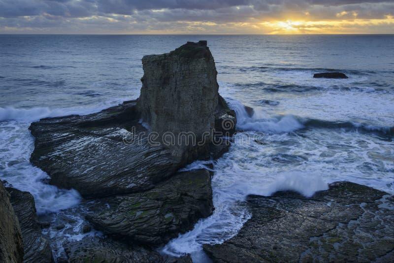Solnedgång på denmil stranden arkivfoto
