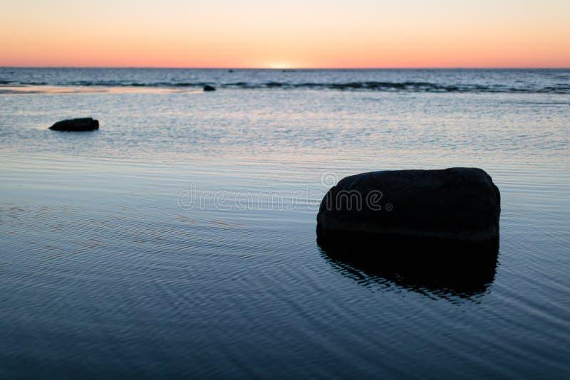 Solnedgång på det lugna havet med stenar fotografering för bildbyråer