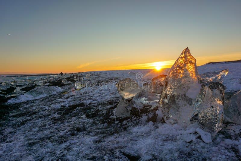 Solnedgång på Diamond Beach In Iceland With glödande stora bitar av is arkivbild