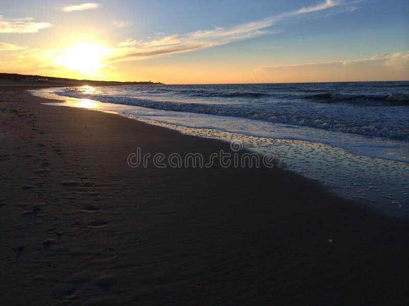 Solnedgång på en holländsk strand arkivbild