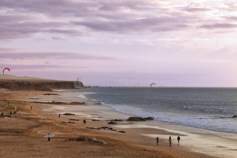 Solnedgång på en sandig strand med drakesurfare arkivfoton