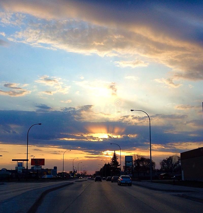 Solnedgång på en stadsgata arkivfoto