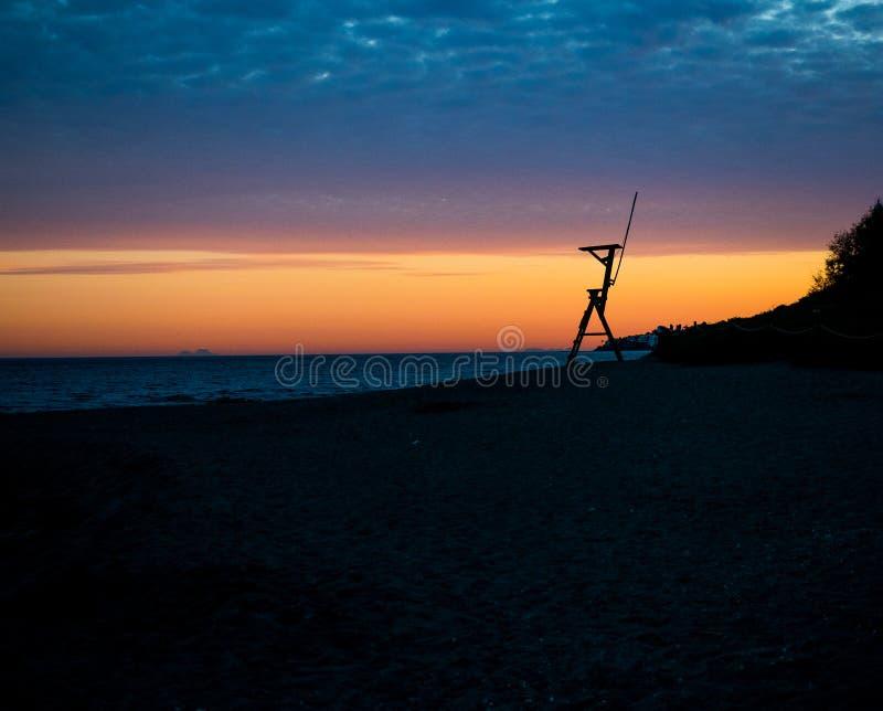 Solnedgång på en strand, bredvid en kust- bevakningstolpe royaltyfri foto